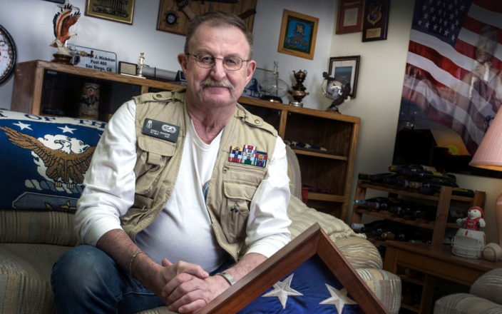 Elderly veteran wearing combat vest and decorations sitting in his home office